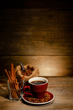 A Cup of black coffee with coffee bean bag and cinnamon on wooden floor Stock Photo