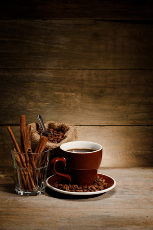 A Cup of black coffee with coffee bean bag and cinnamon on wooden floor, composition for book cover