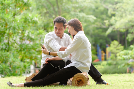 Man and woman in white shirt use smartphone together in outdoors park
