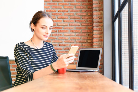 Woman freelance in coffee shop use smartphone and laptop