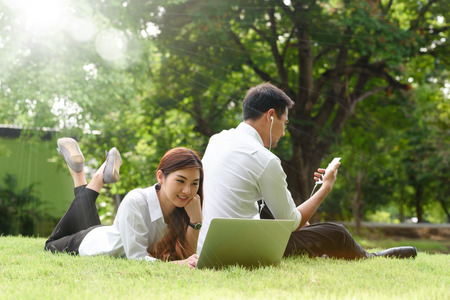 Man and woman in white shirt use smartphone and laptop together in outdoors park