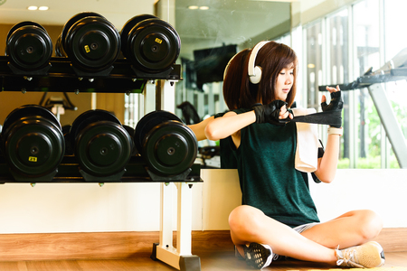 Sport woman wearing on black glove with on-ear head phone in gym