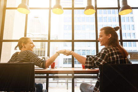 man and woman freelance make fist bump in coffee shop on one fine day in the afternoon