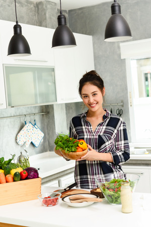 Healthy Young beautiful asian woman preparing vegetable for salad in kitchen
