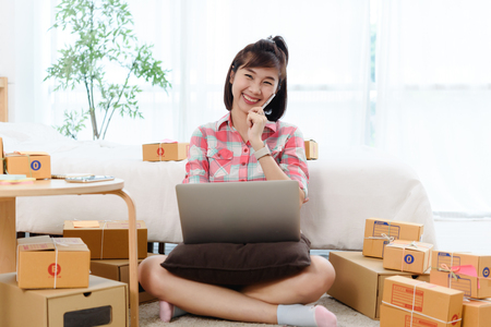 Happy Woman small business owner, business start up in bedroom, young entrepreneur work with laptop prepare parcel boxes for deliver to customer
