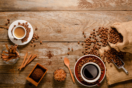Top view of espresso shot and a cup of americano with coffee bean bag, sugar and cinnamon on wood background floor