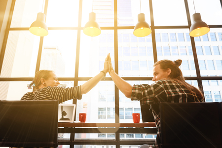 man and woman freelance make hi five in coffee shop on one fine day in the afternoon Stock Photo