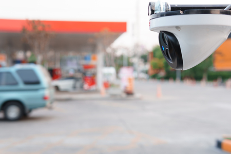 CCTV surveillance camera operation in gas station with cars parked