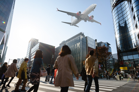 Scene of airplane over city with people cross road