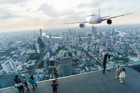 Scene of airplane over city with sun light and light ray over city of Bangkok