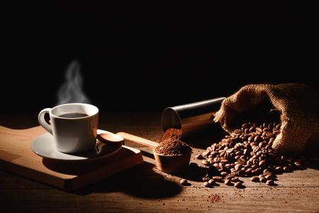 Un bicchierino di caffè espresso con chicco di caffè tostato e macinacaffè in alluminio