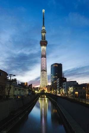 Tokyo sky tree, the tallest building in Japan with light of car run on street and reflection in water from canal at sunset