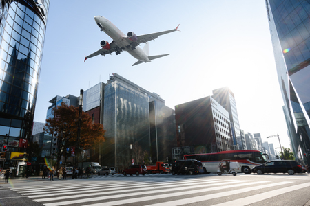Scene of airplane over city with traffic cars