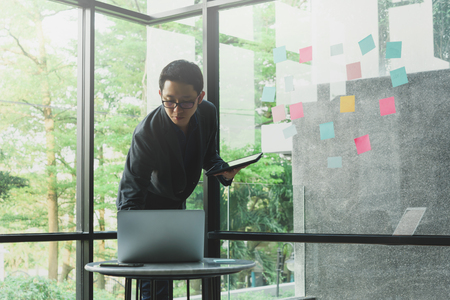 Businessman use laptop and tablet while take note and put on sticky notes on glass wall