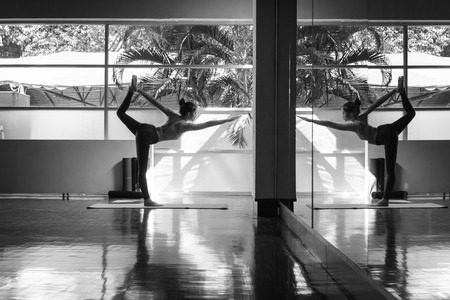 Young asian woman practicing yoga performing Lord of the Dance Pose black and white scene with reflection in mirror