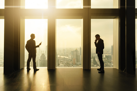 Two business man use smartphone by window on sky scrapper 版權商用圖片