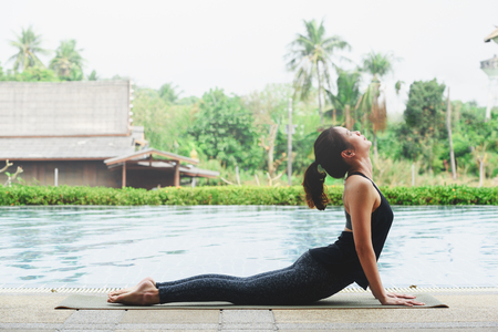 Young asian woman practicing yoga performing upward-Facing Dog Pose beside swimming pool