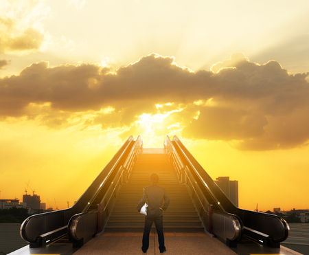 Businessman stand on top of staircase with sun light on open sky, success businessman conceptual