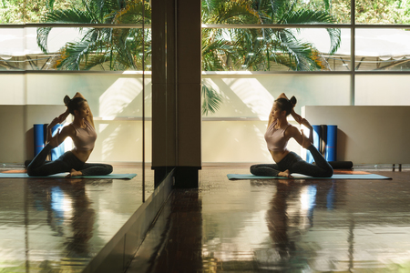 Skinny good looking asian woman practicing yoga alone in studio room with reflection in mirror 版權商用圖片