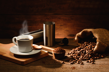 A shot of espresso with roasted coffee bean and alumenium coffee grinder