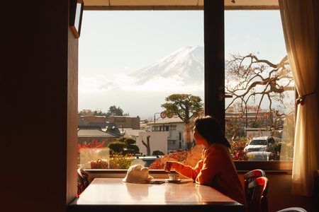 Young asian woman admire view of fuji mountain by window in hotel have coffee in m orning