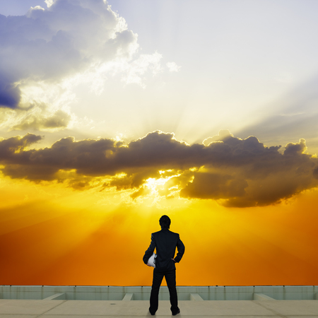 businessman stand on roof top of skyscrabber with beautiful twilight sky