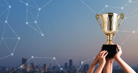 Gewinnerteam hebt Trophäenbecher mit digitalem Hintergrund, digitale Leistung konzeptionell Standard-Bild