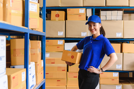 Portrait of woman delivery staff in blue uniform holding parcel box size D in warehouse 免版税图像 - 126727399