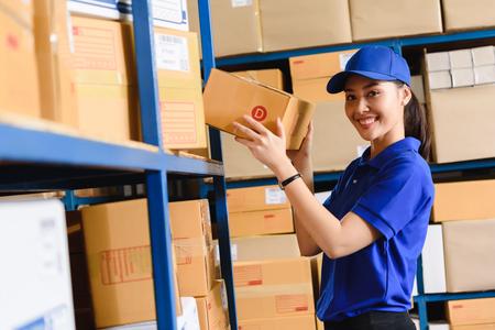Ritratto di donna addetta alle consegne in uniforme blu che tiene una cassetta dei pacchi taglia D in magazzino in Archivio Fotografico