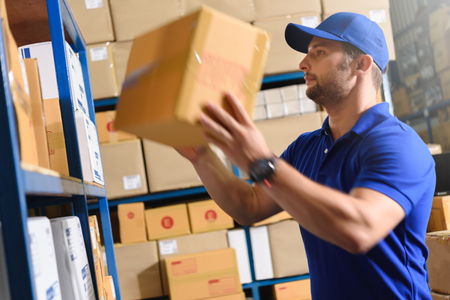 Portrait of delivery staff in blue uniform looking for particular box in warehouse 版權商用圖片