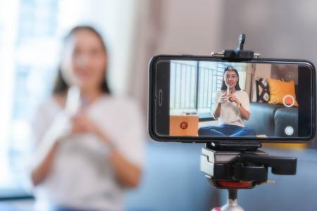 Bloguera de belleza que demuestra cómo maquillar y revisar productos en una transmisión en vivo usando un teléfono inteligente, la vida de un influencer