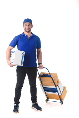 Delivery man in blue uniform of delivery service thumb up with trolley, online shopping delivery concept