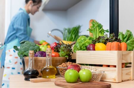 Pile of healthy food consist of vegetables, fruits and nuts with young woman washing fruits in background Stockfoto