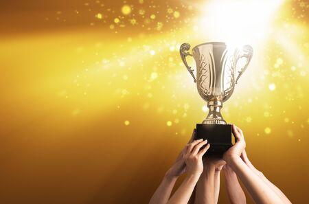 Winnend team heft trofeebeker op met achtergrond van lucht van lichtstraal