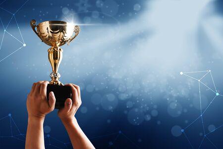 L'équipe gagnante soulève la coupe du trophée avec un fond de ciel de rayon lumineux Banque d'images