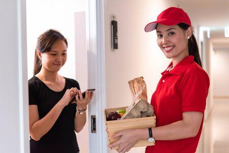 Le personnel de livraison livrant de la nourriture au client qui a commandé en ligne signe sur smartphone pour recevoir des produits