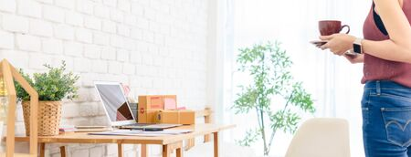 Scene of woman hold coffee cup walk to work desk with laptop and small parcel box, home office dimension photo for banner