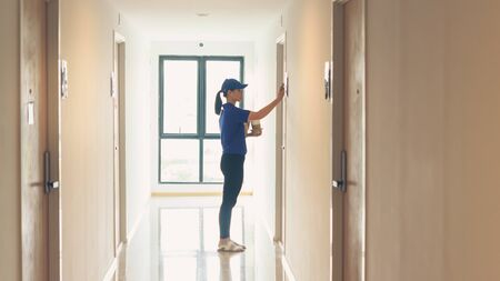Woman delivery staff delivering coffee knock on apartment door
