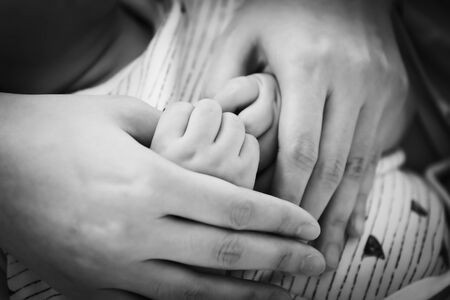 Hands of parent hold their child making heart shape in black and white tone