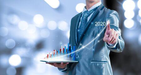 empresario sosteniendo un informe de tableta sobre el crecimiento del gráfico virtual de negocios. Planificación estratégica empresarial para el año 2020 conceptual. Foto de archivo
