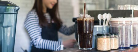Ice americano on coffee counter with young business owner working in background, dimension image for banner
