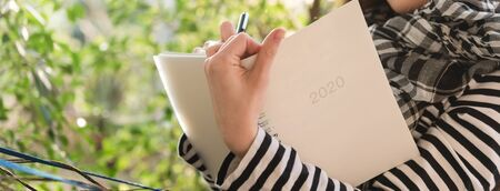 teenage woman write note plan for 2020 in white notebook, dimension image for banner
