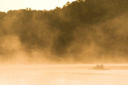 La gente sale su una zattera di bambù, avventura mattutina in inverno con nebbia che galleggia sull'acqua di superficie