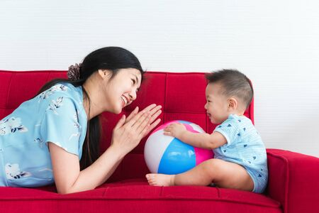 Mother play with her 8 month old son in blue dress on red sofa bed