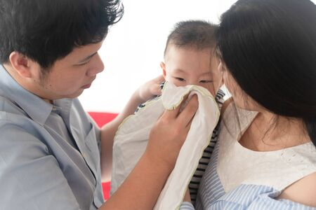 Father and mother take care of their baby have flu, sneeze and cough and have snot in nose