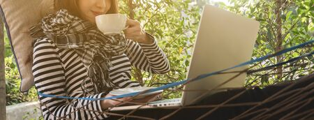 Young woman having coffee in hammock while use laptop, freelance life style conceptual, work anywhere, dimension image for banner