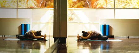 Young asian woman prepare for yoga training by streching back and legs with very flexible body reflection in window Stok Fotoğraf