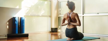 Skinny good looking asian woman practicing yoga alone in studio room Stok Fotoğraf