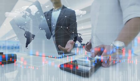 Two businessman work with laptop and diagram of stock market exchange technology