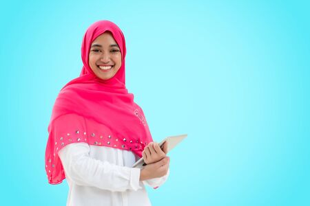 Young muslim woman hold tablet wear pink hijab scarf on blue background